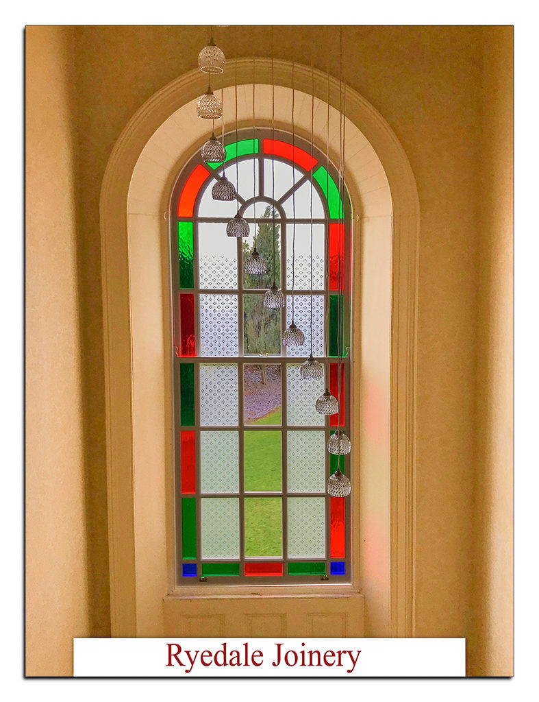Elegant arched sash window with etched and coloured double-glazed panels fitted.